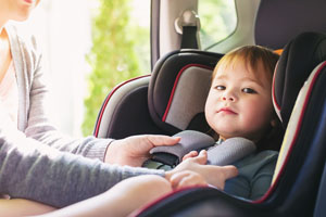Mother buckling child in car seat